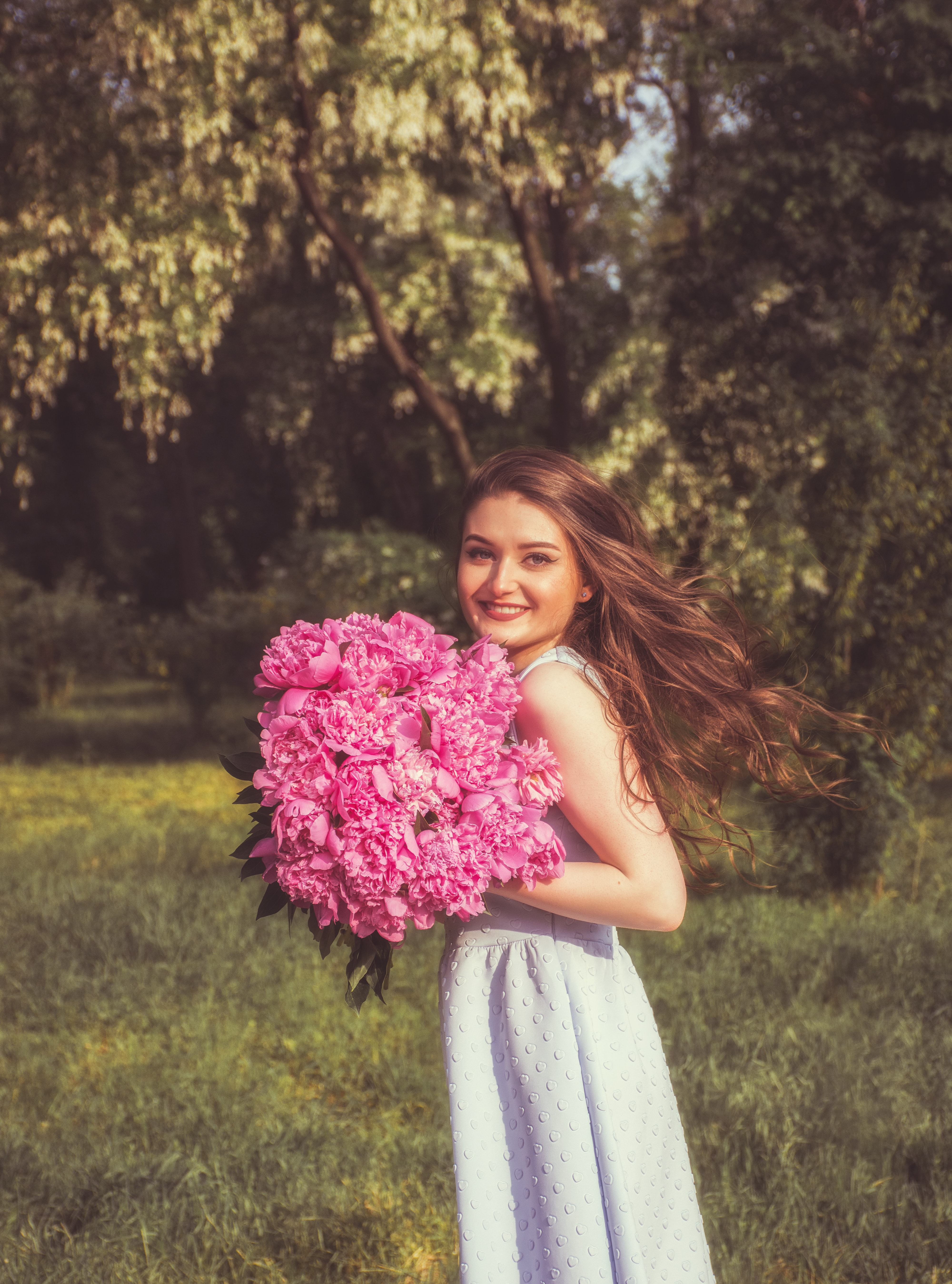 woman holding bouquet of pink flower smiling during daytime