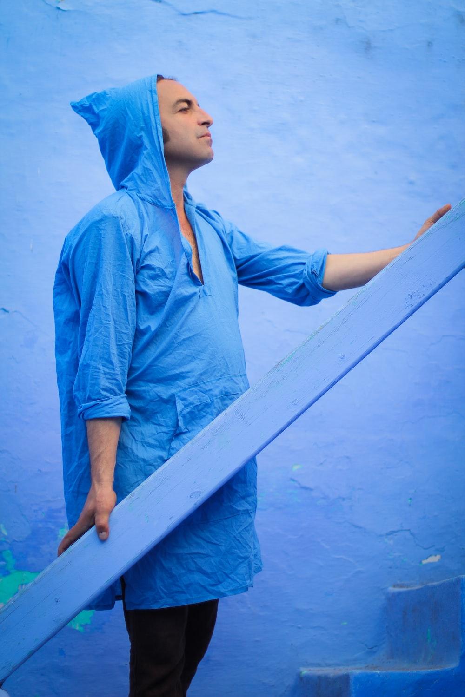 man holding blue plank