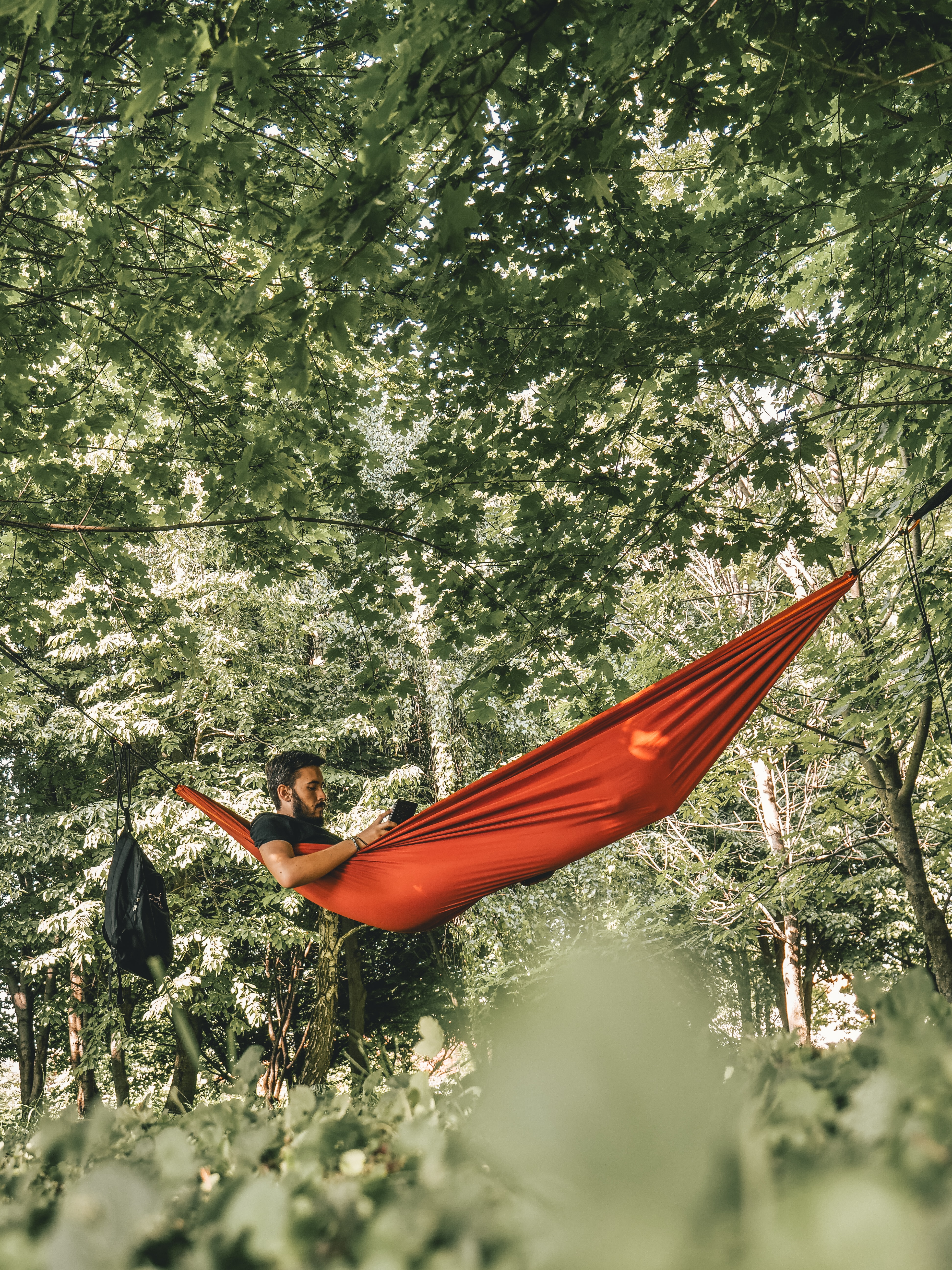 man on red hammock surrounded by trees during daytime