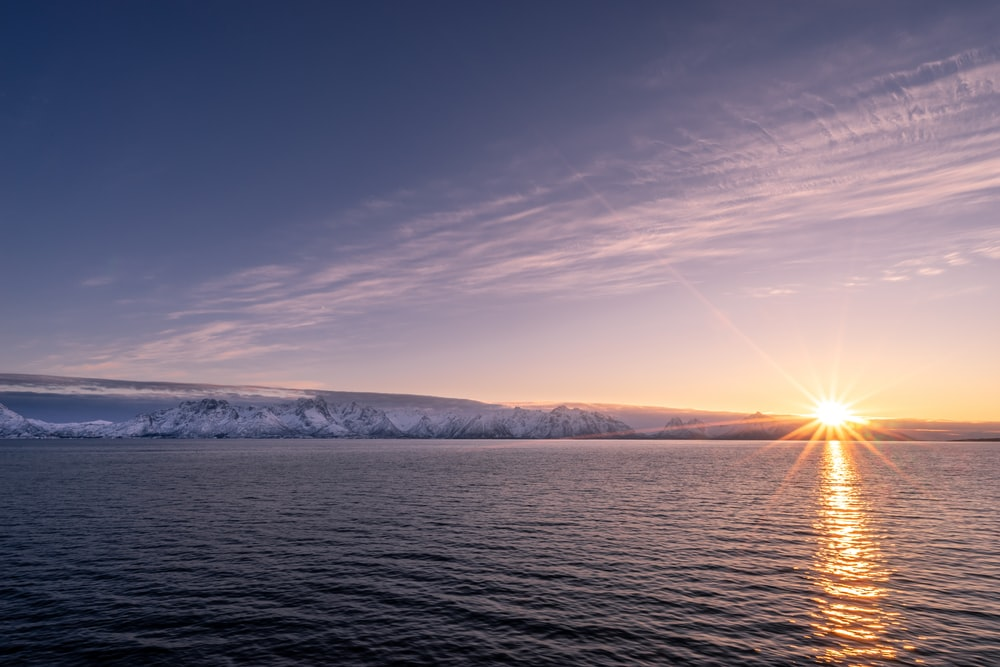 calmly body of water over mountain under blue sky at sunset