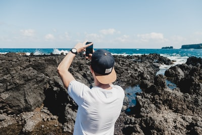 man holding black smartphone while taking a photo of open sea maui teams background