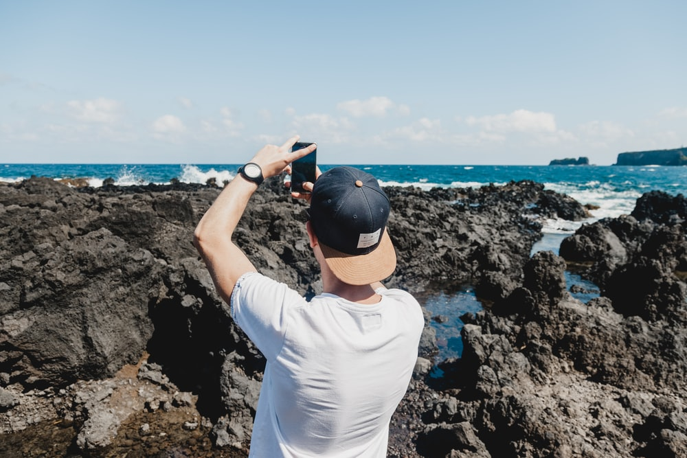 man holding black smartphone while taking a photo of open sea