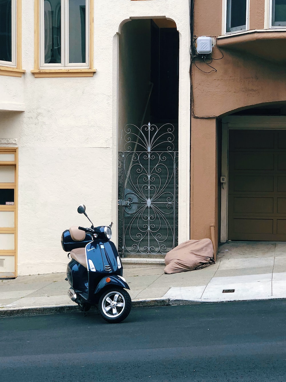 black motor scooter parked near beige concrete house