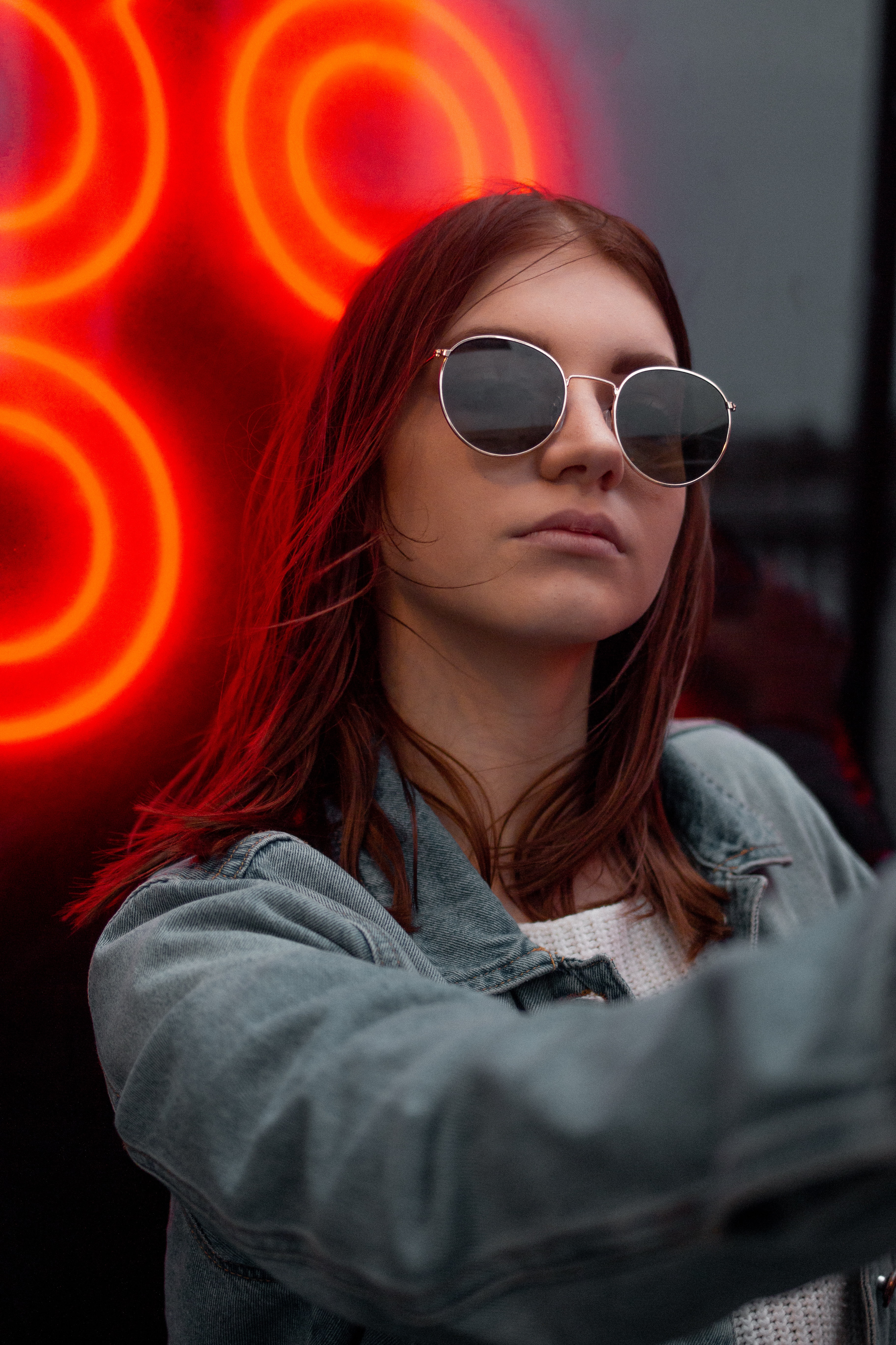 woman wearing silver-colored framed sunglasses and blue denim collared jacket