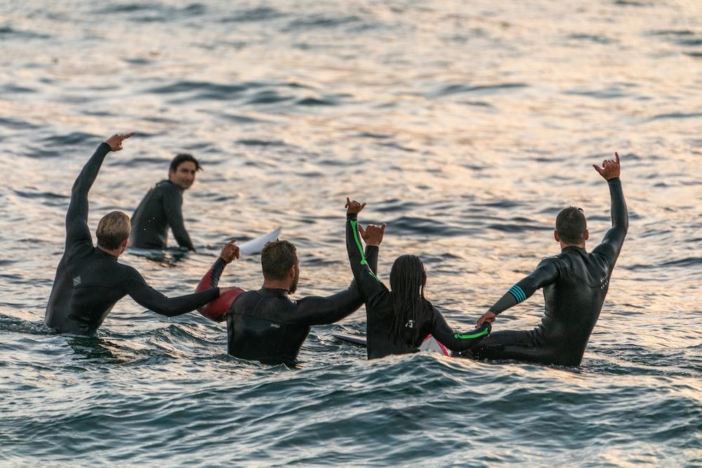 people wearing black wetsuits in body of water