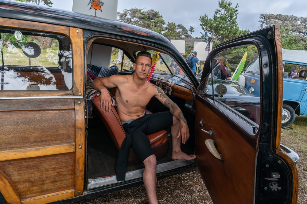 man sitting on brown leather vehicle seat during daytime