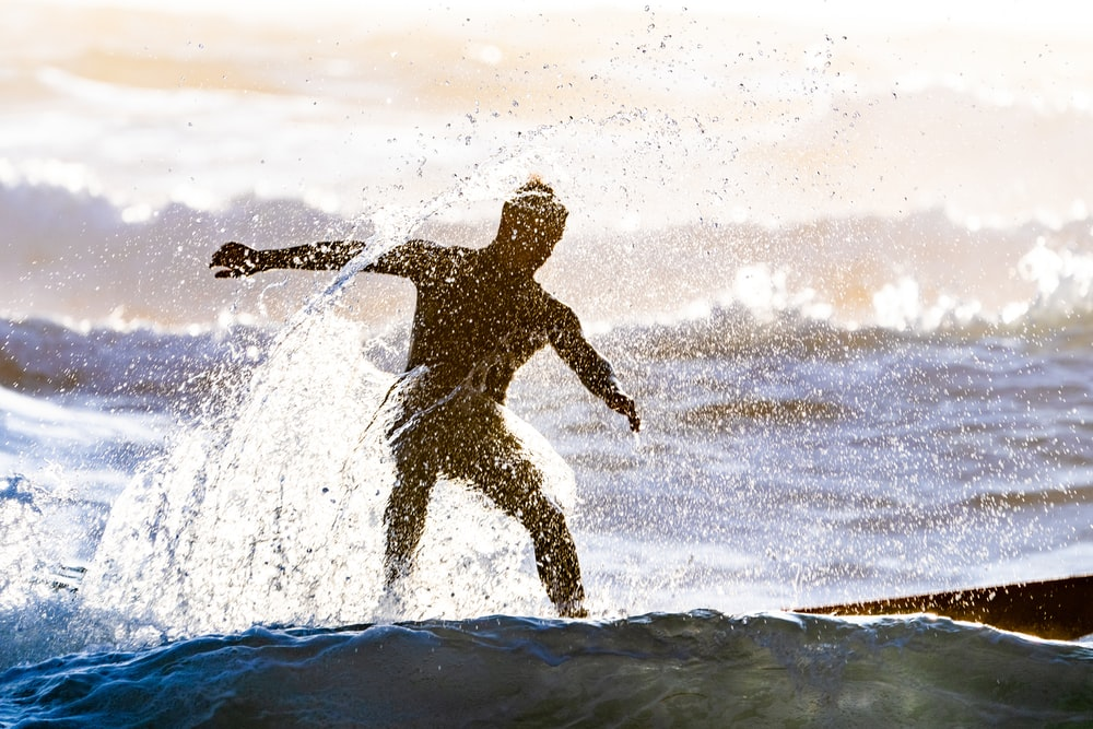 silhouette photography of man surfing on body of water