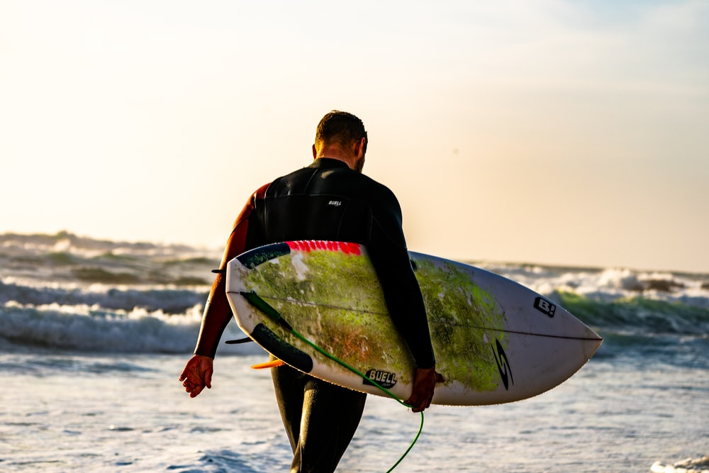 man carrying white surfboard while walking towards sea with waves during daytime
