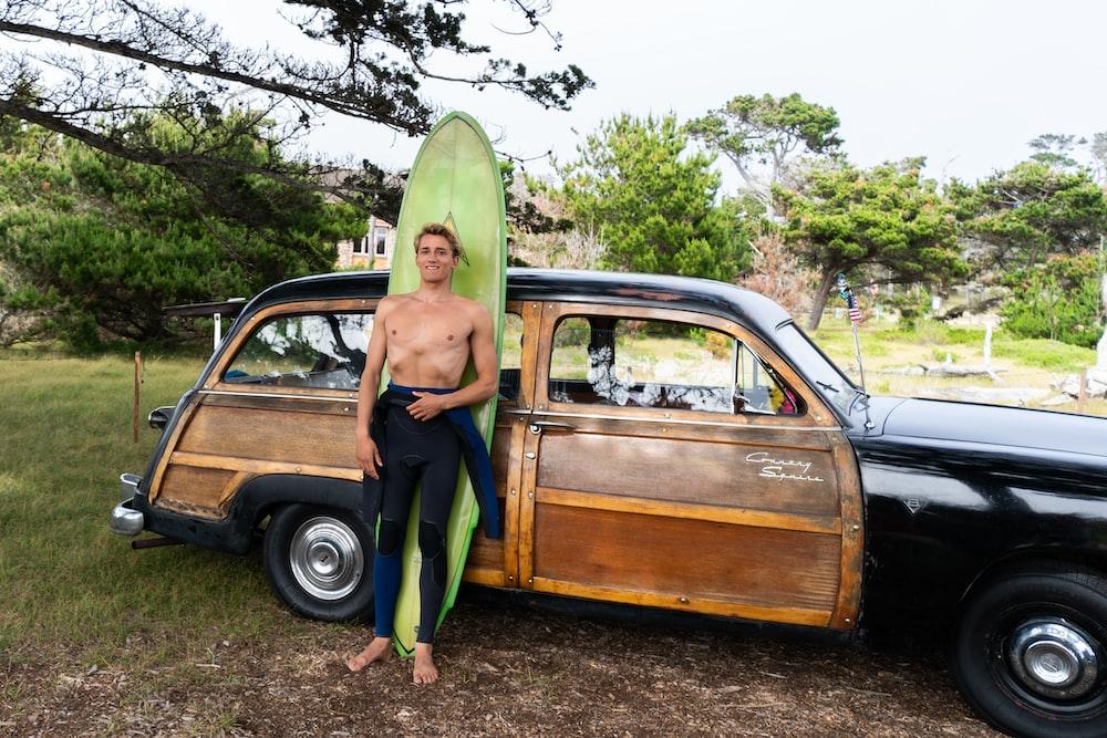 man standing beside car leaning on green surfboard