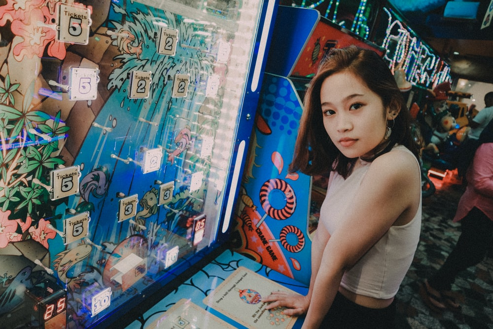 woman wearing white top standing in front on the blue slot machine