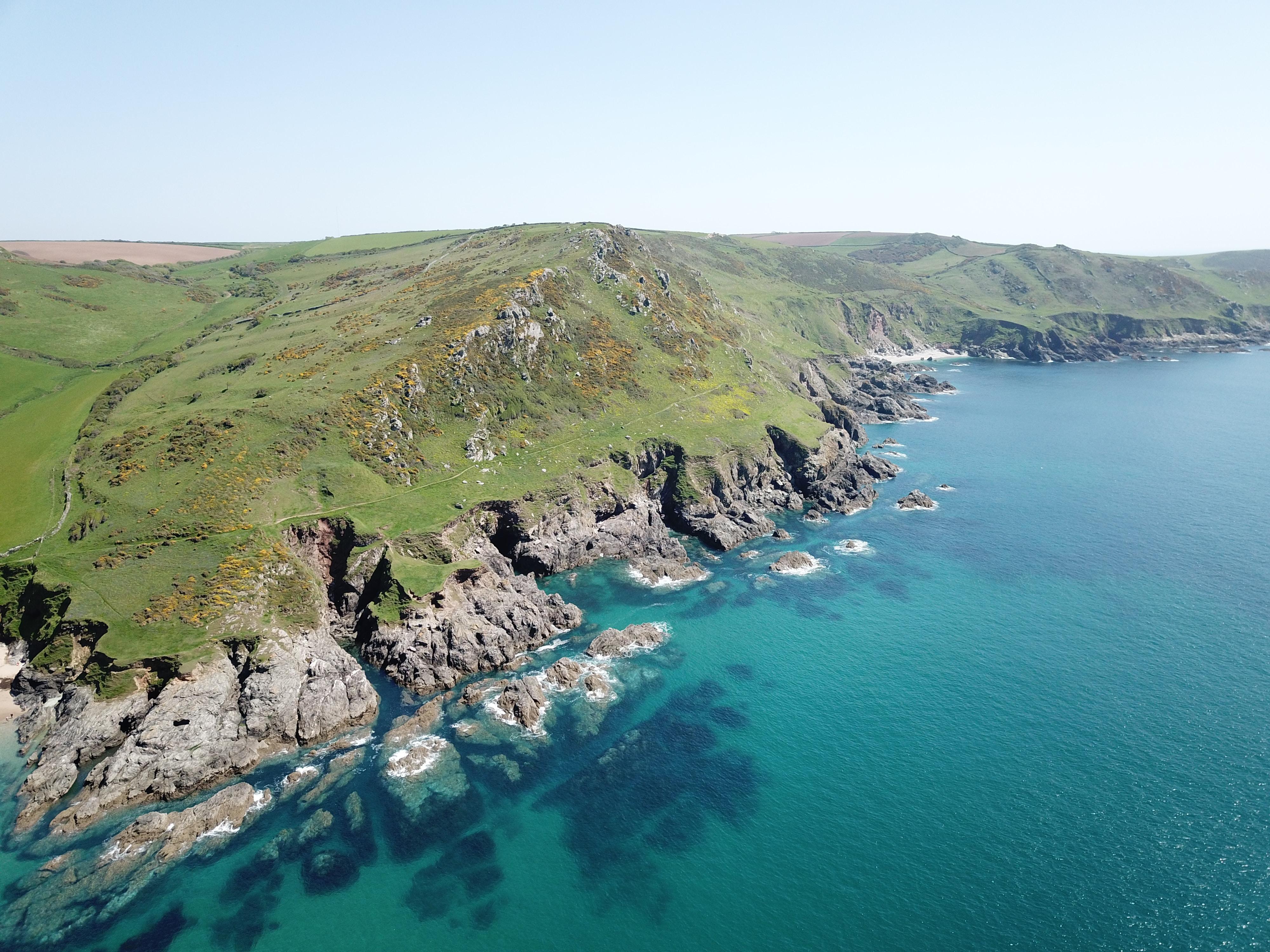 calm body of water beside rock coastal with green fields