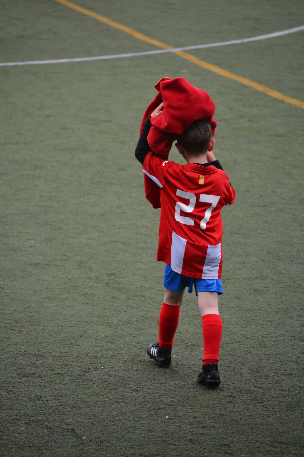 boy wearing red and white 27 soccer jersey shirt