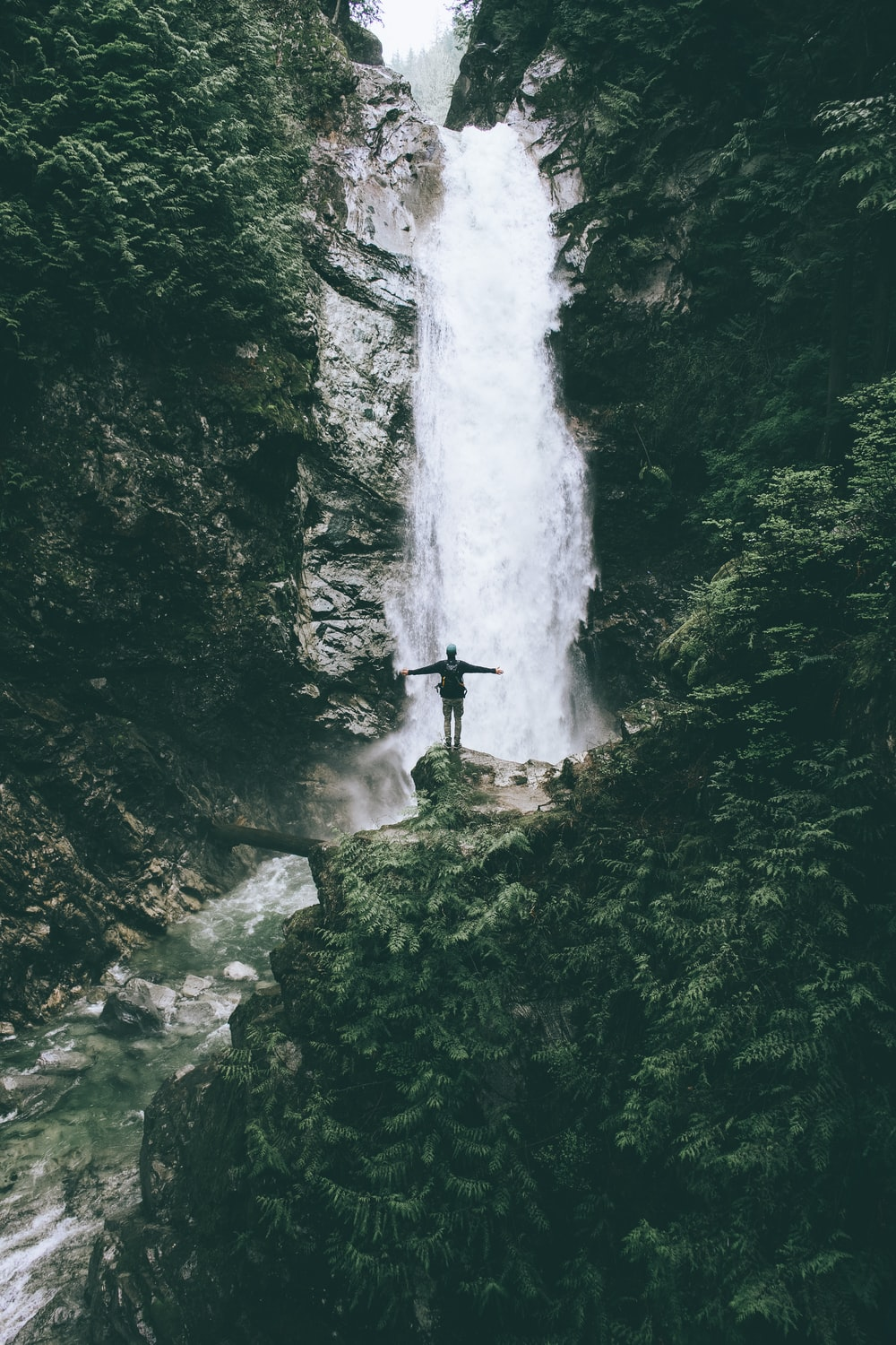 man standing at the cliff in front of the fall