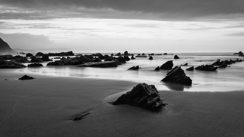 grayscale photo of big rocks surrounded by body of water