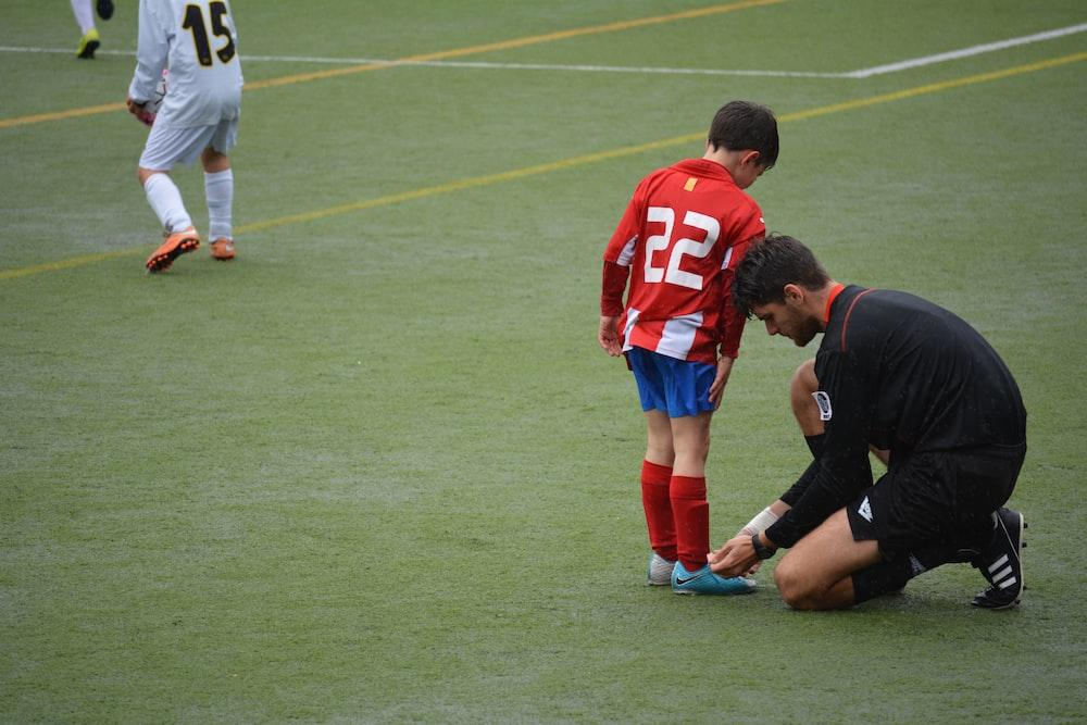 man tying boy's shoes on field