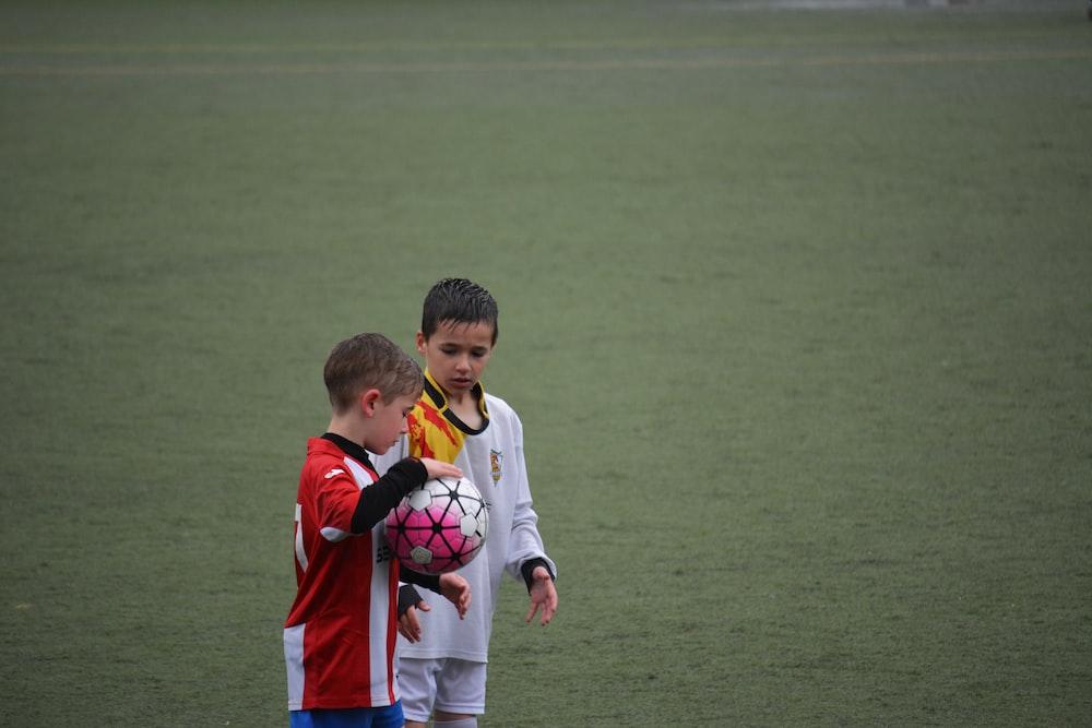 boy holding soccer ball beside other ball on soccer field
