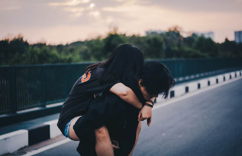 woman piggyback on man standing on gray concrete road during daytime