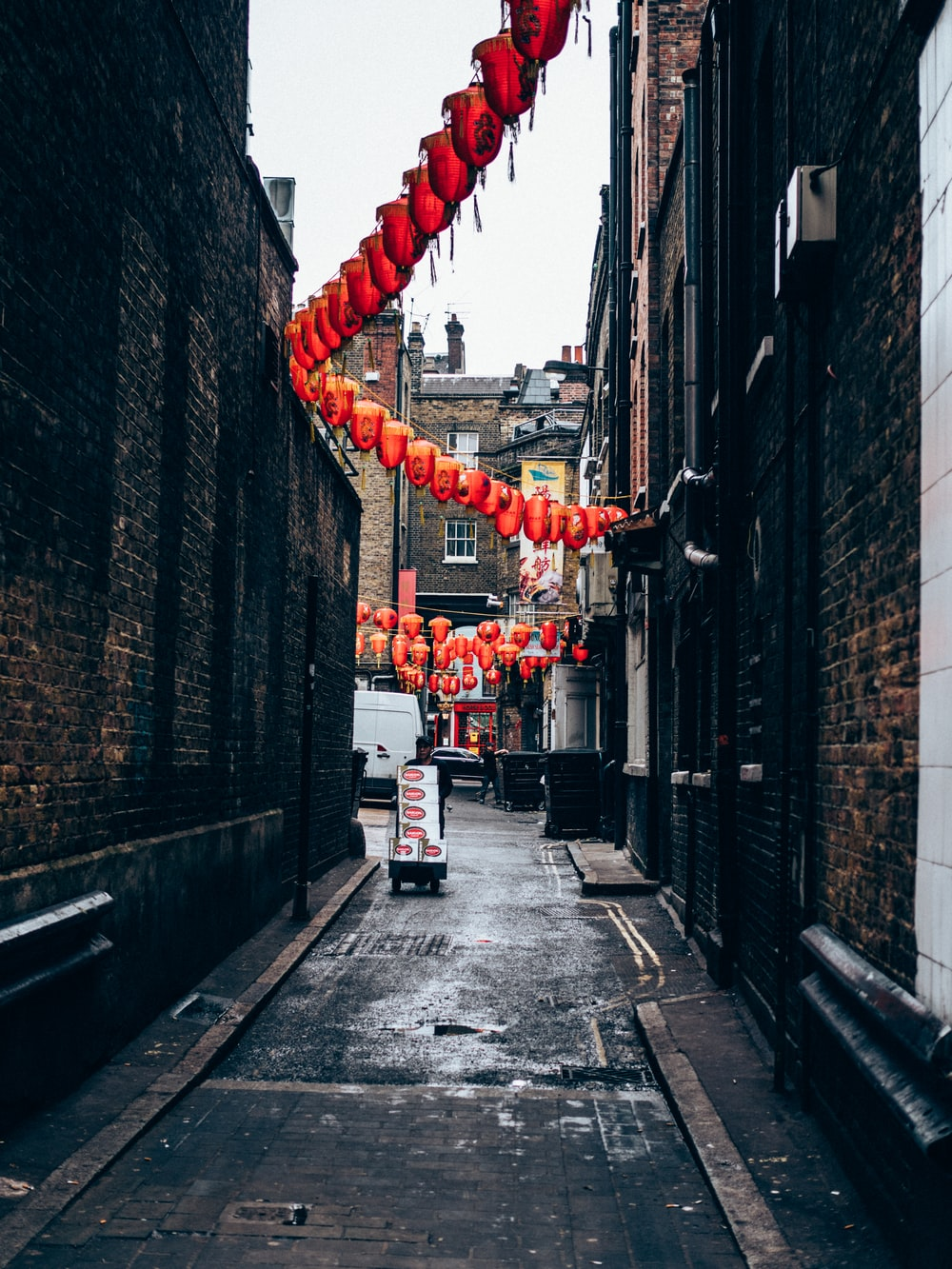 red Chinese lantern hanged on gray concrete buildings during daytime