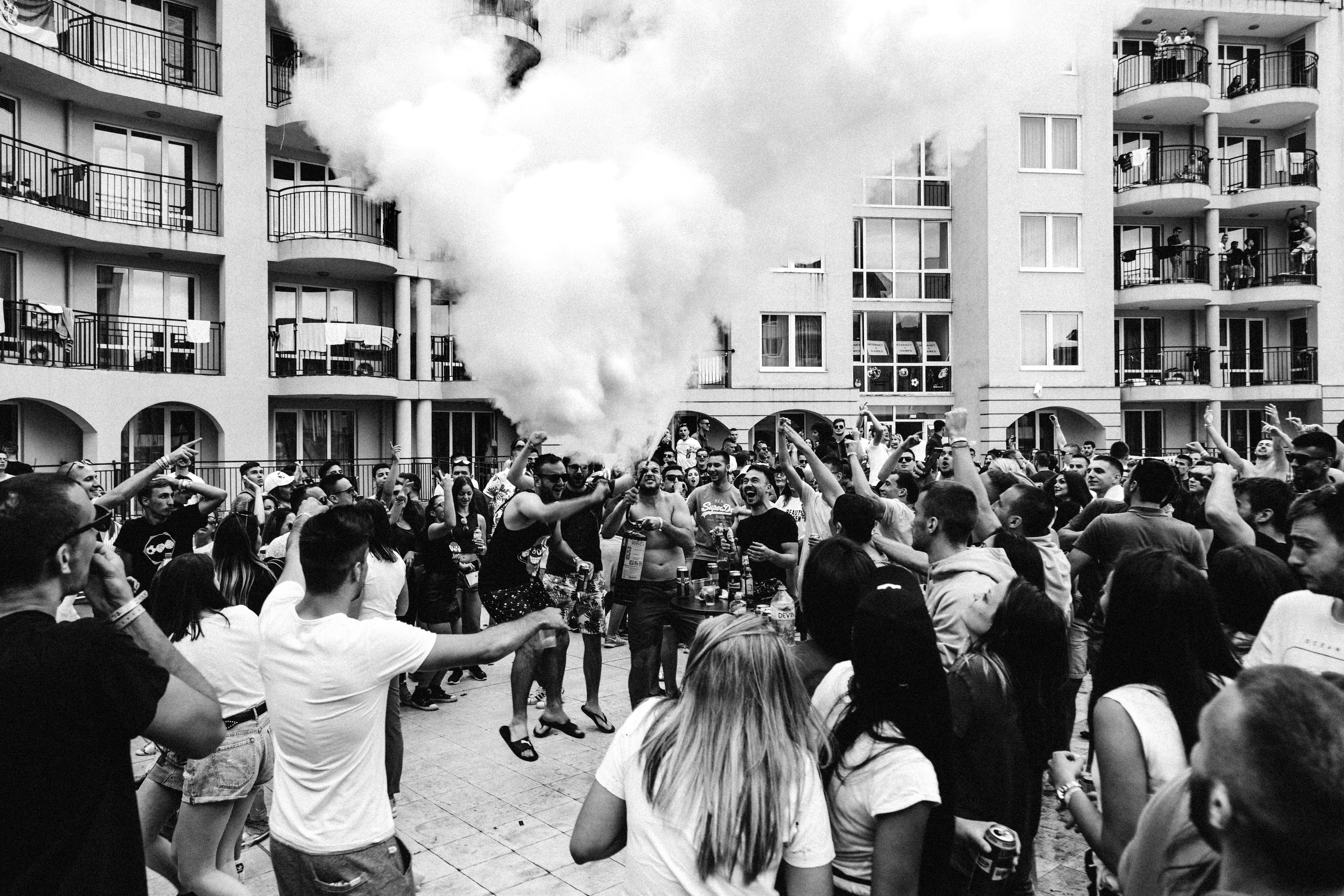 crowded people on road on grayscale photo