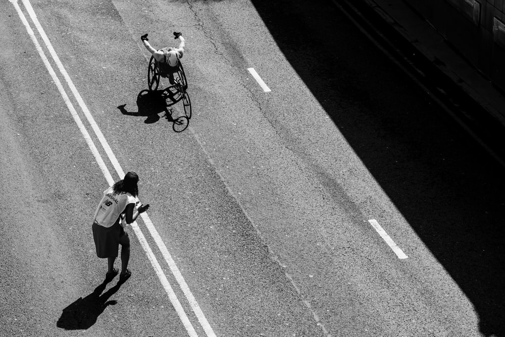 person standing on the road grayscale photography