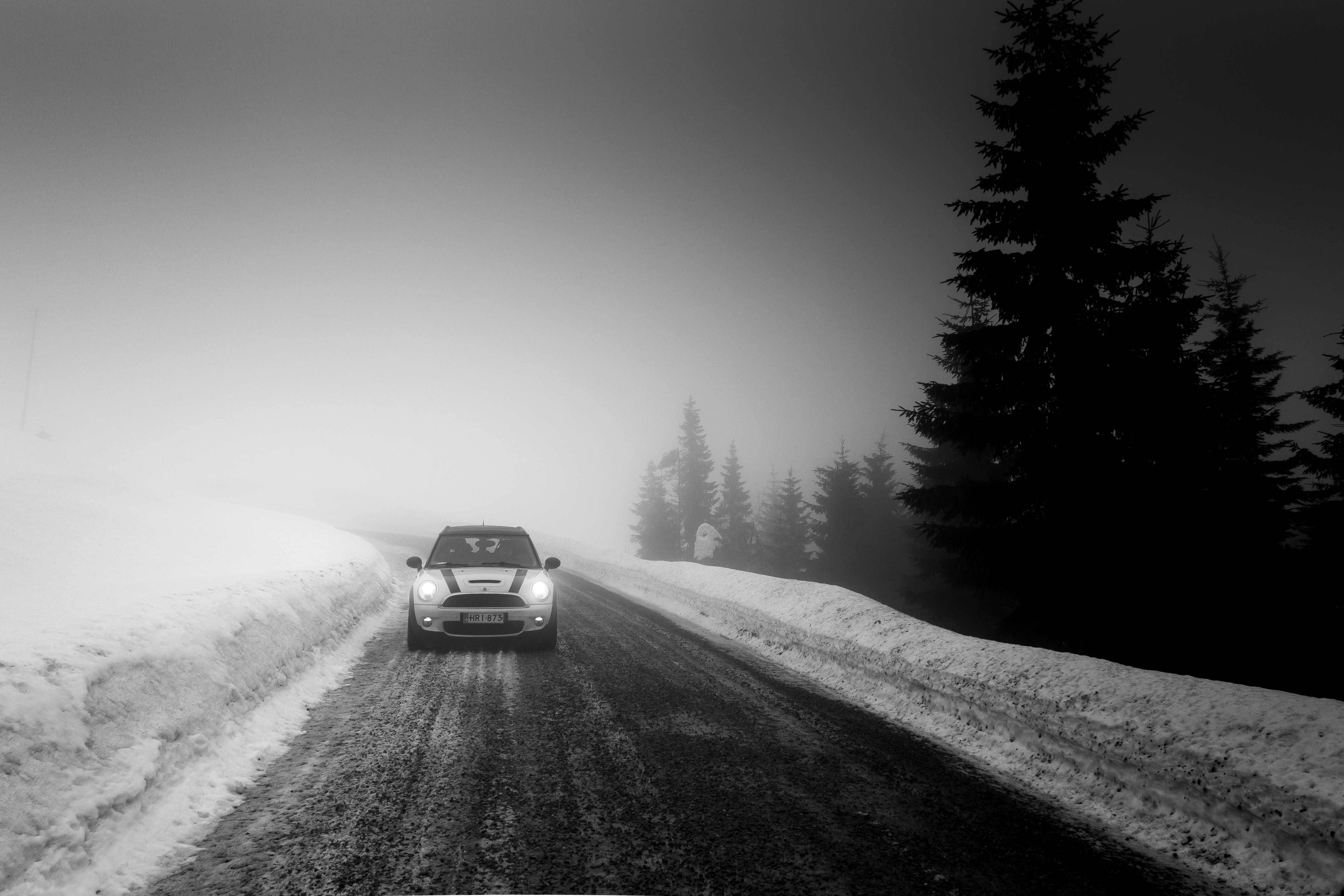 grayscale photo of car in between snow and tree