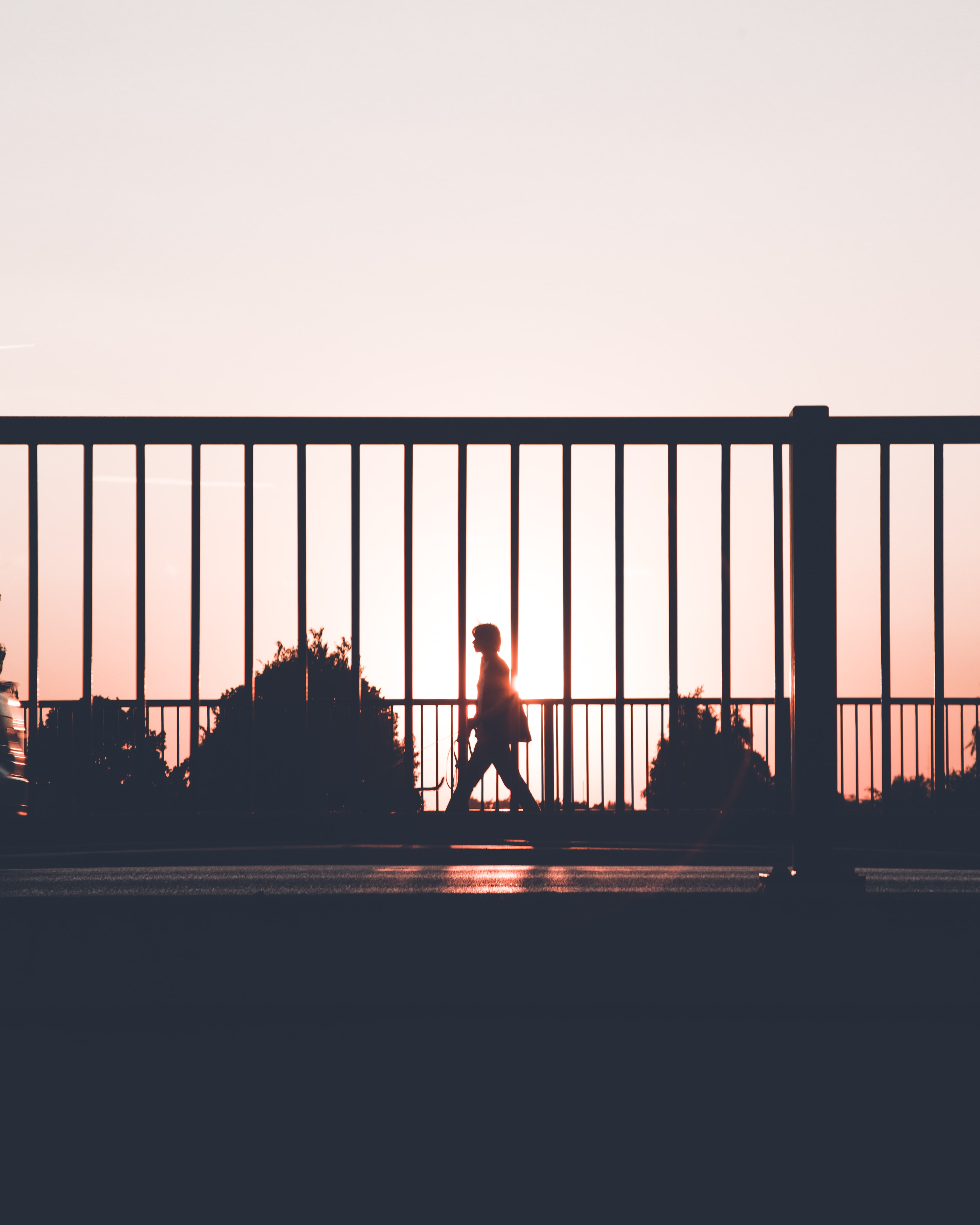silhouette of person walking on roadside during sunset