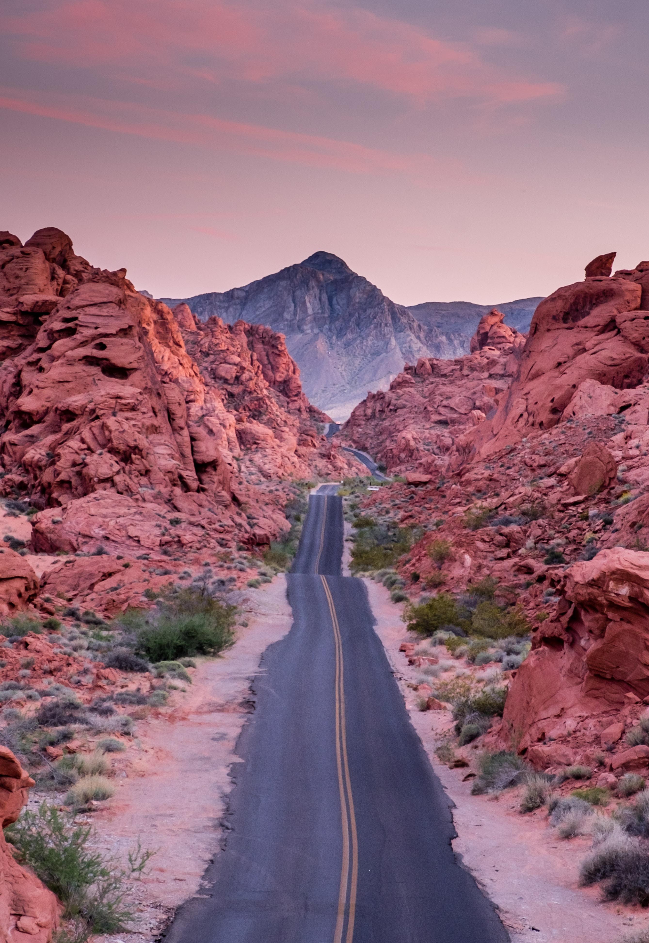 photo of empty road between rock formations