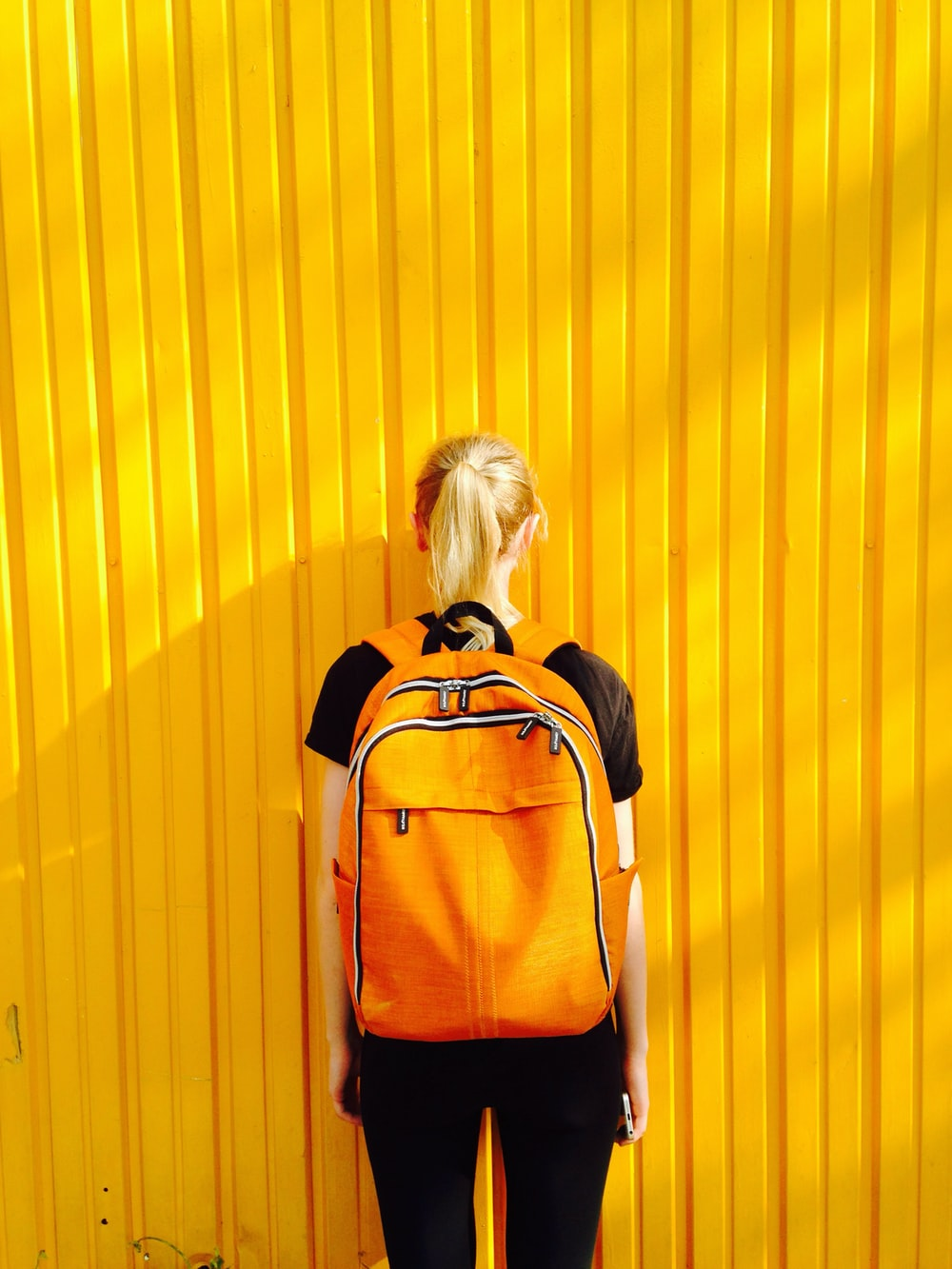 photo of woman facing yellow wall