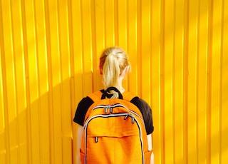 photo of woman facing yellow wall