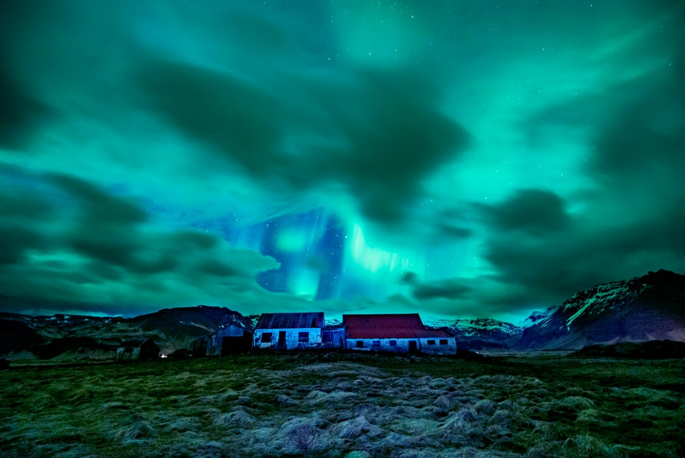 landscape photography of green nebula and houses