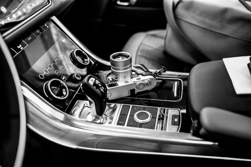 grayscale photo of SLR camera on vehicle center console