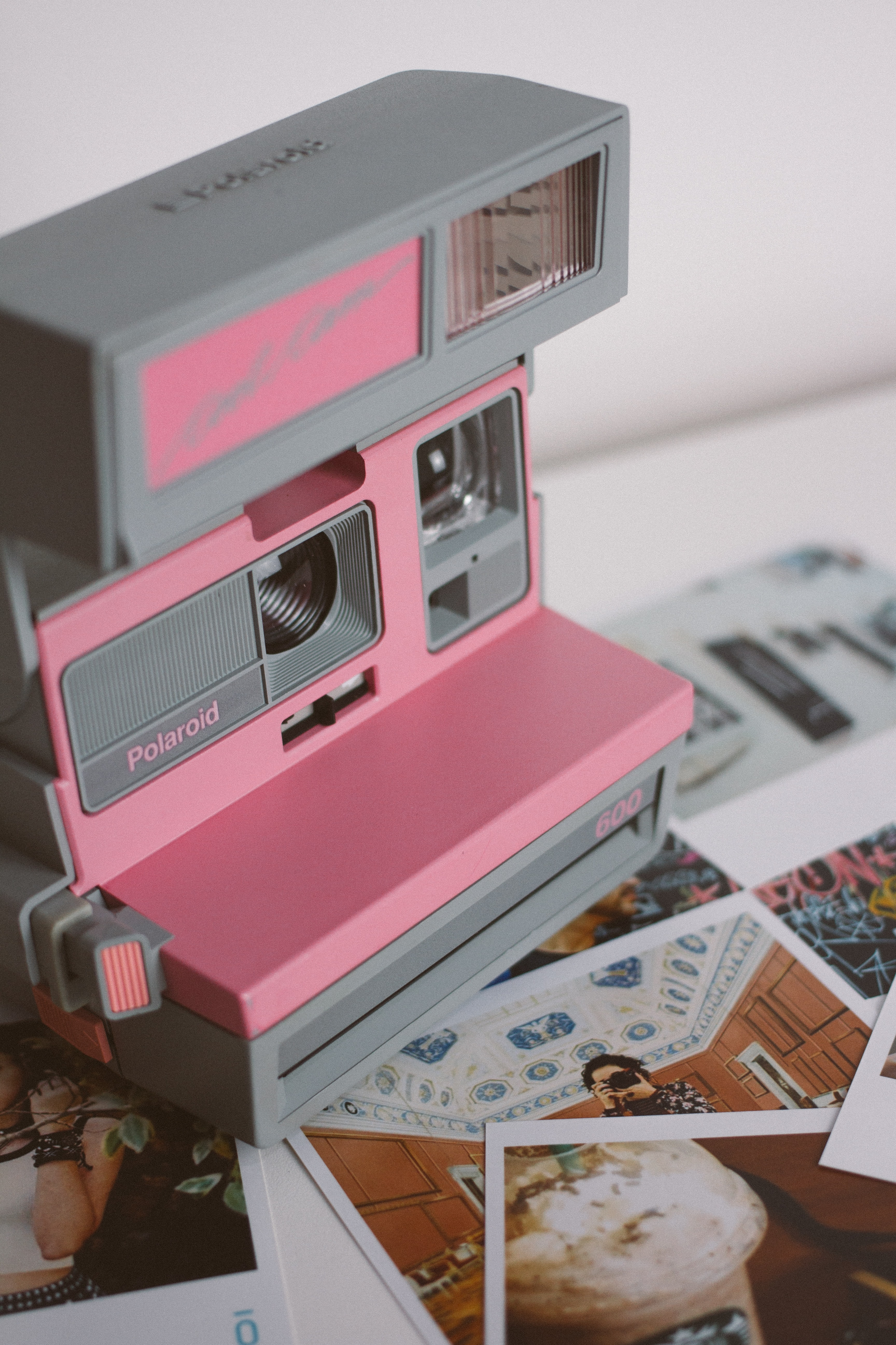 selective focus photography of gray and pink Polaroid land camera