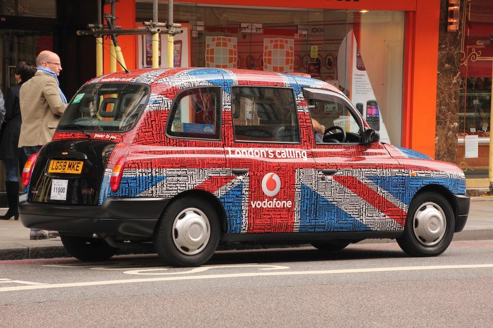 United Kingdon flag-themed 5-door hatchback on gray concrete road