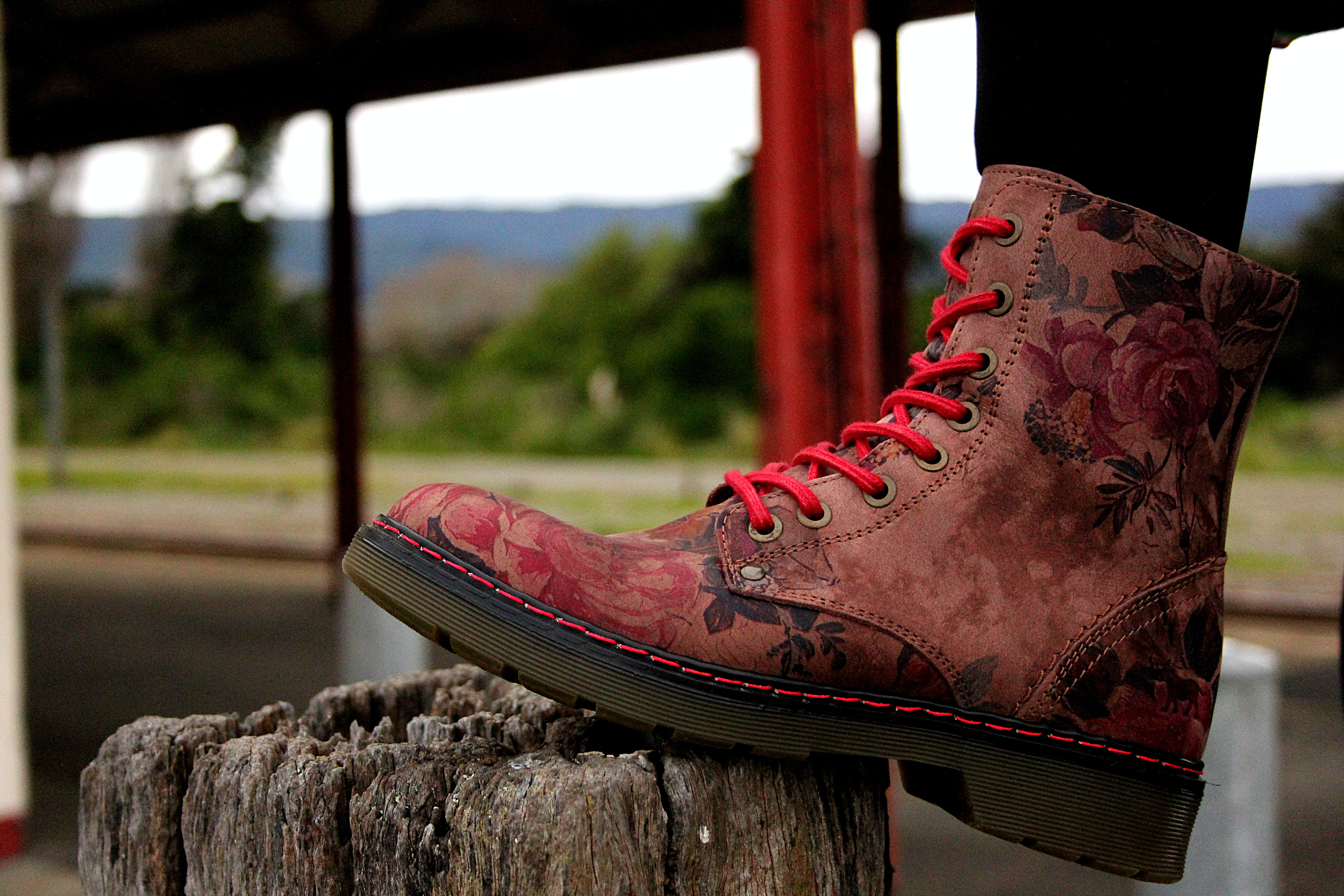unpaired brown and red floral leather boot on foot