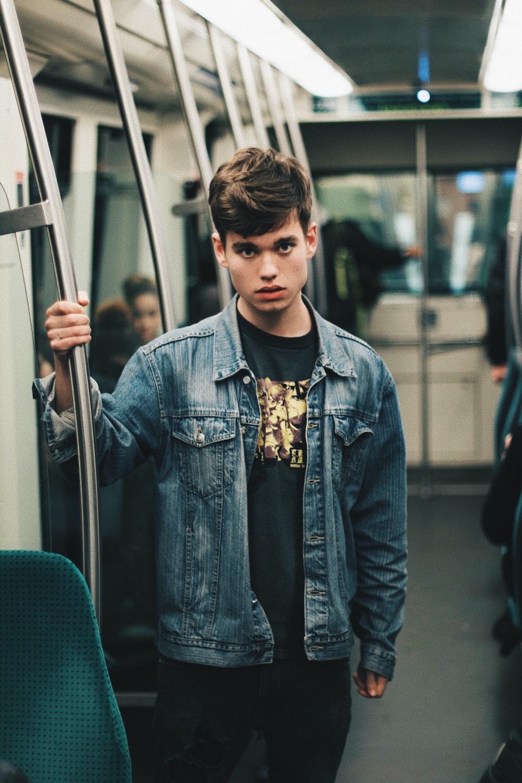 man wearing blue denim jacket standing inside train