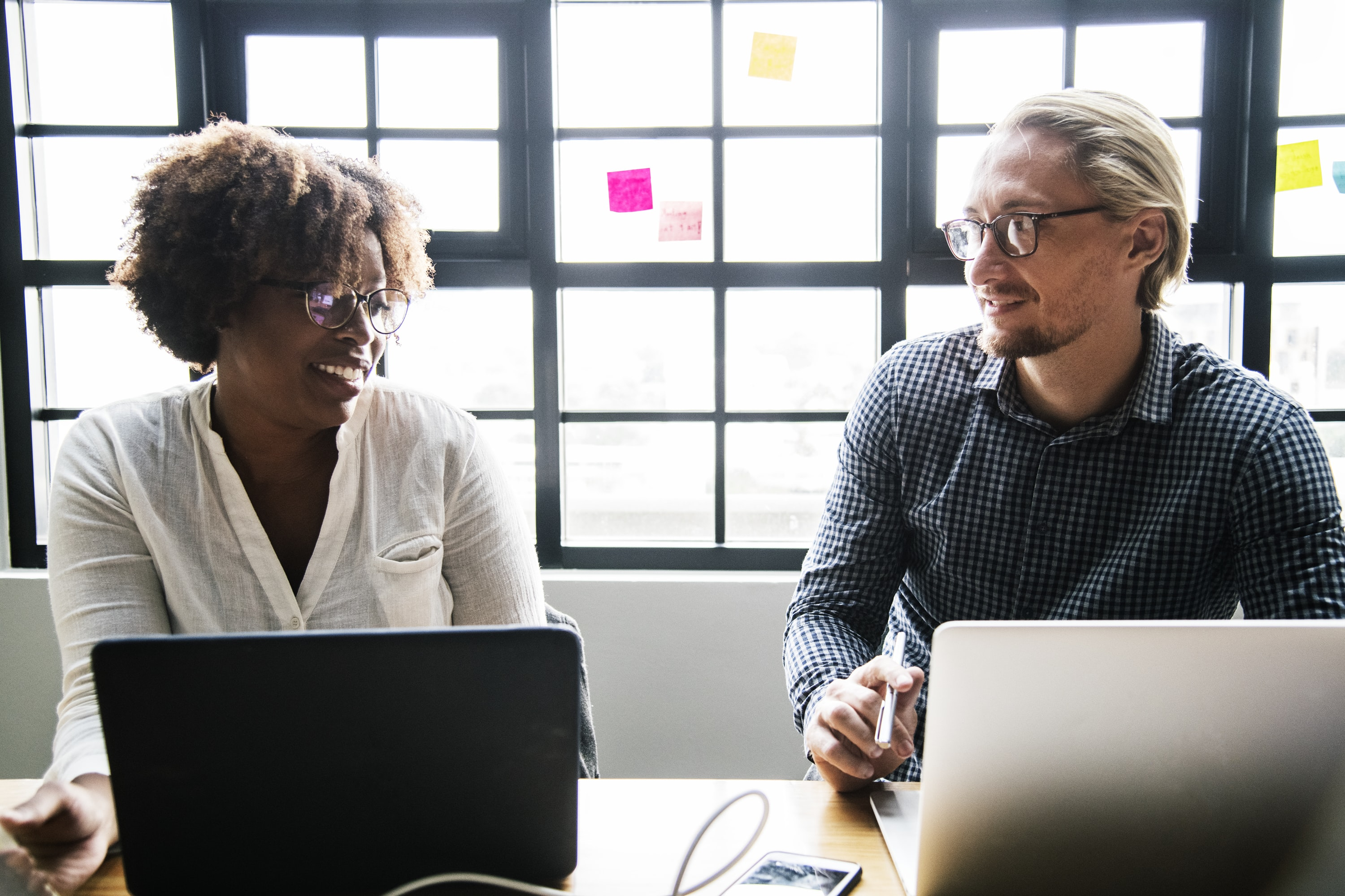 man and woman talking in front of laptops