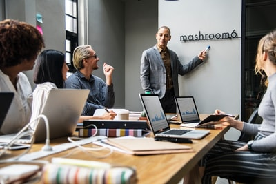 person showing to people the Mashroom6 signage inside room