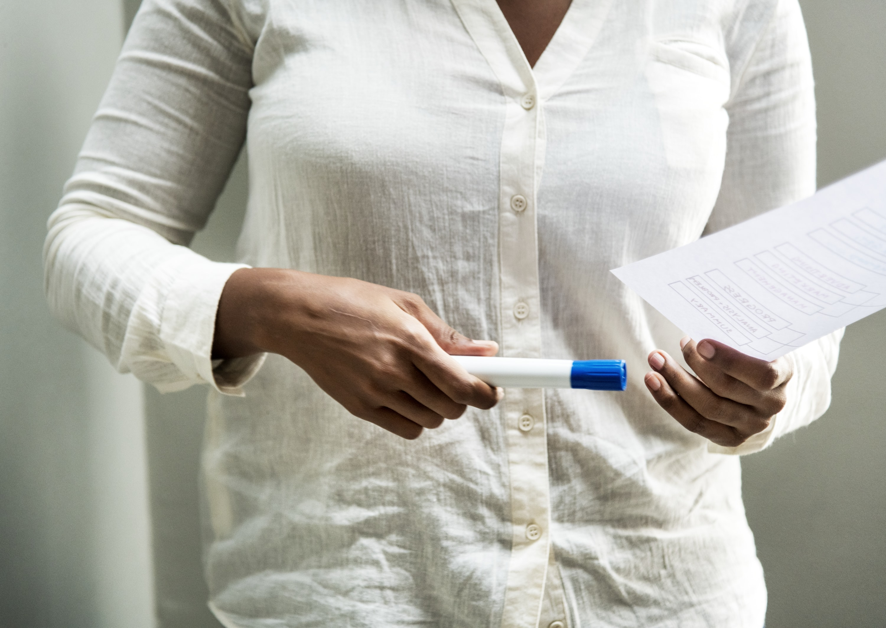 woman holding marker and paper