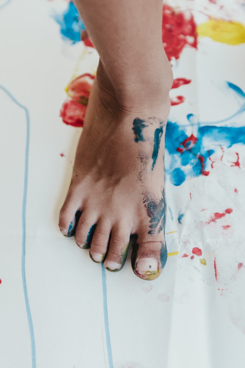 person his right foot painting on white paper