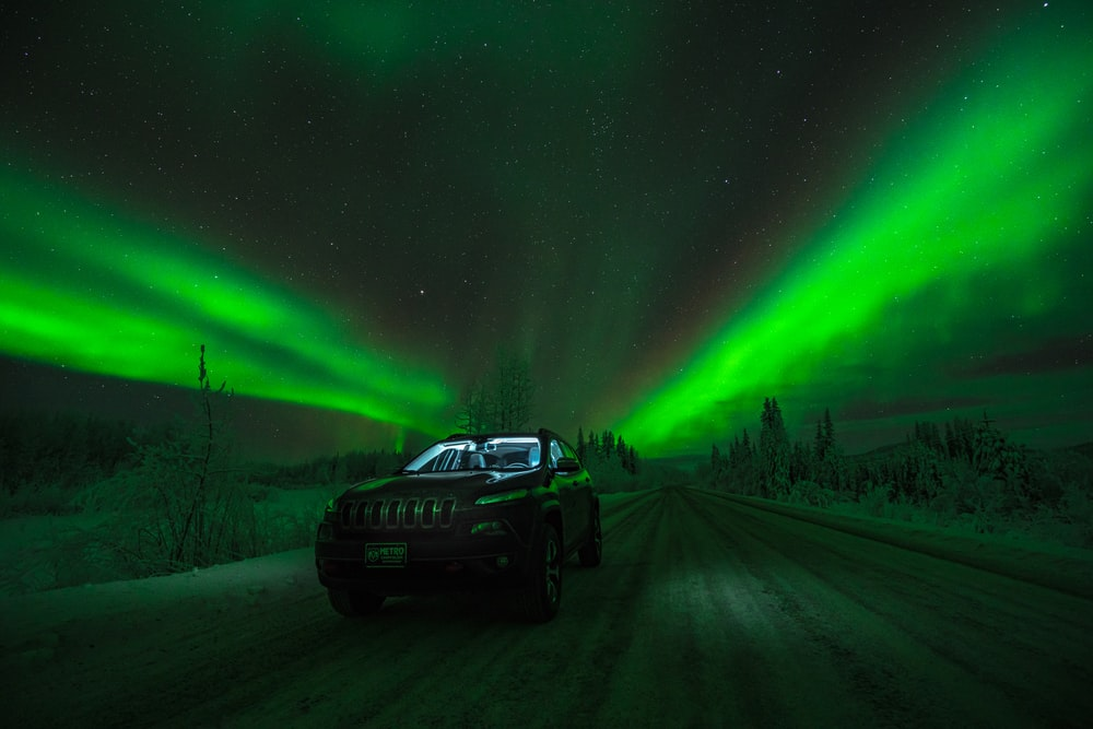 black car on road under Aurora Borealis