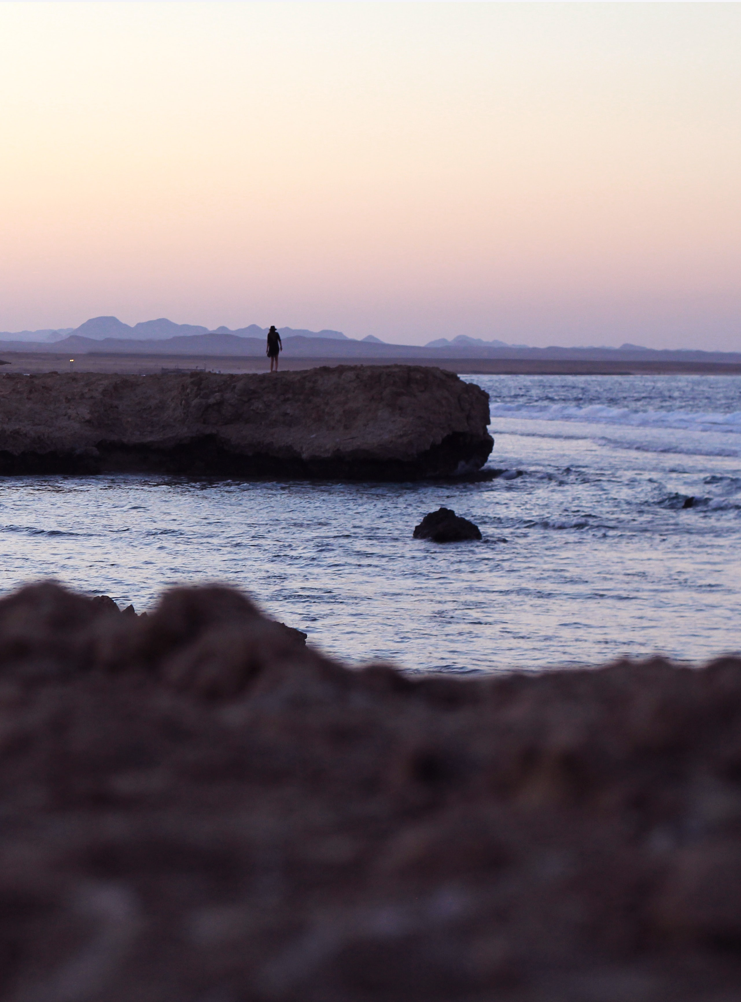 person standing on cliff near body of water