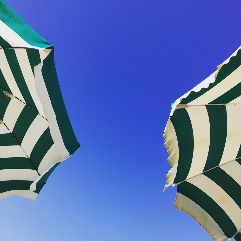 worm's-eye view photography of two green and white patio umbrella under blue sky during daytime