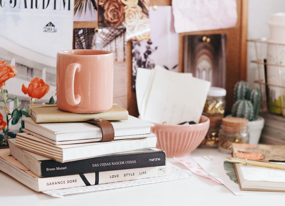 brown ceramic coffee mug on book