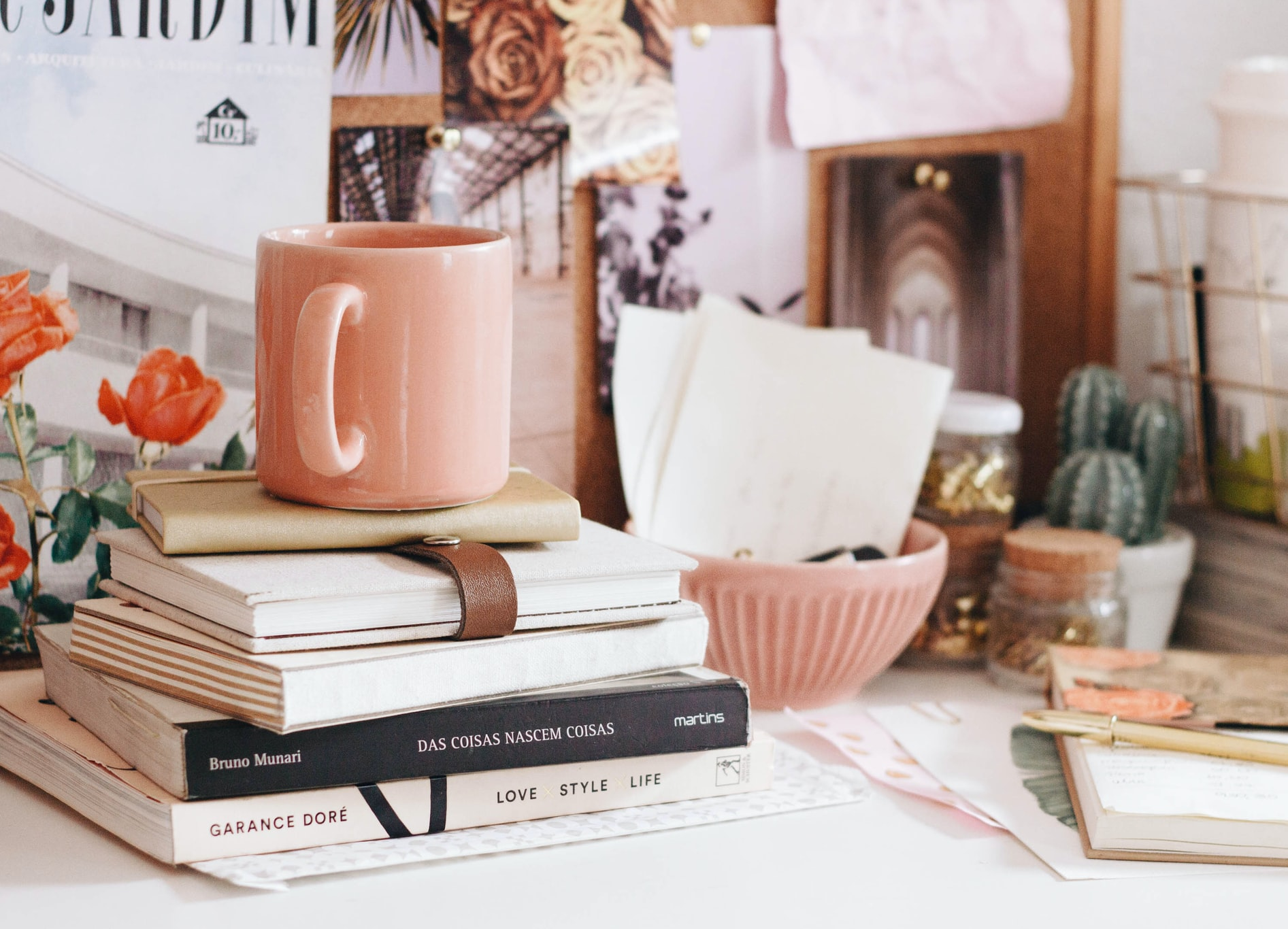 A stacked pile of assorted books with a peach coloured coffee cup on top.