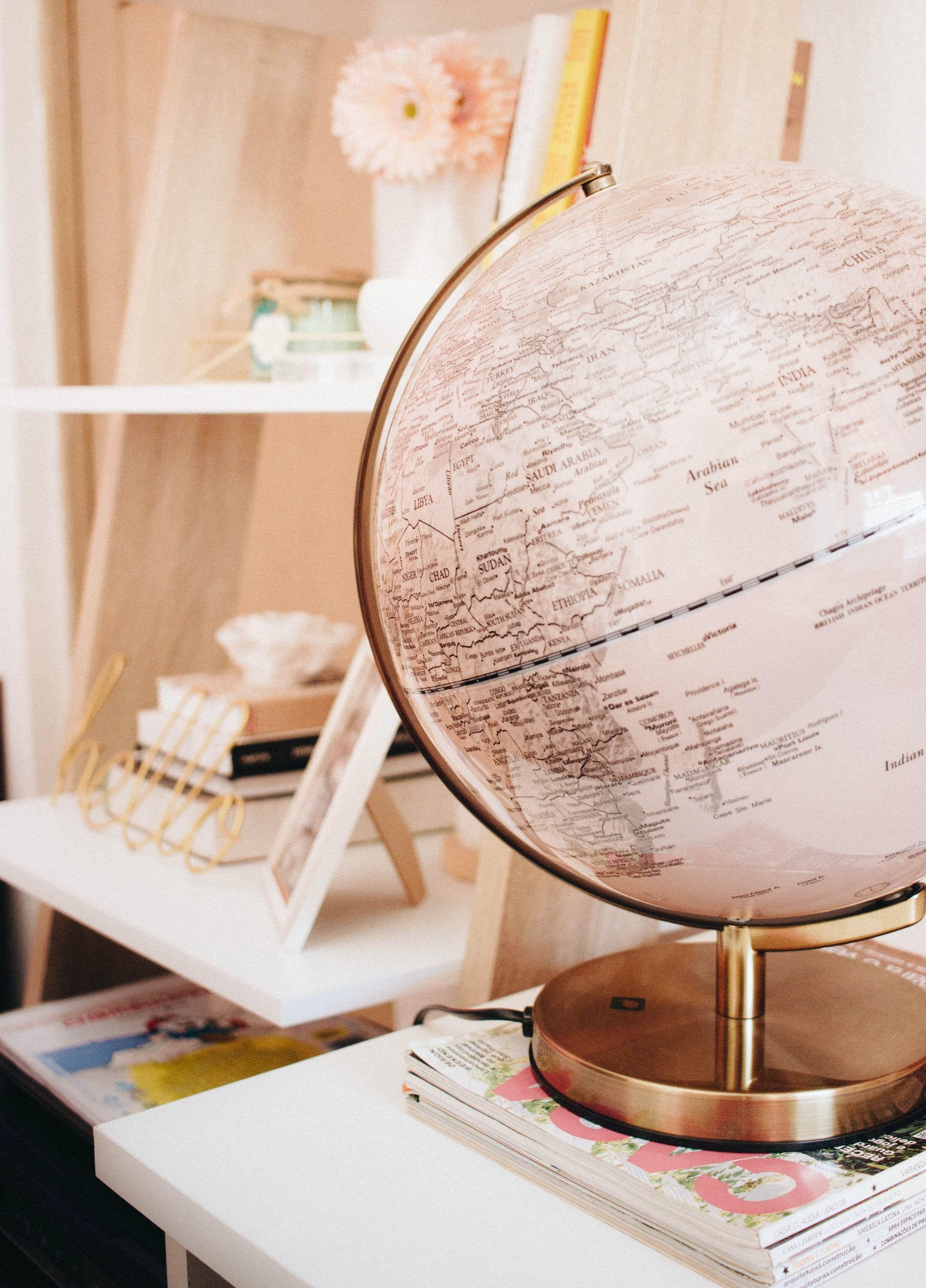 white and black desk globe on the top of magazines
