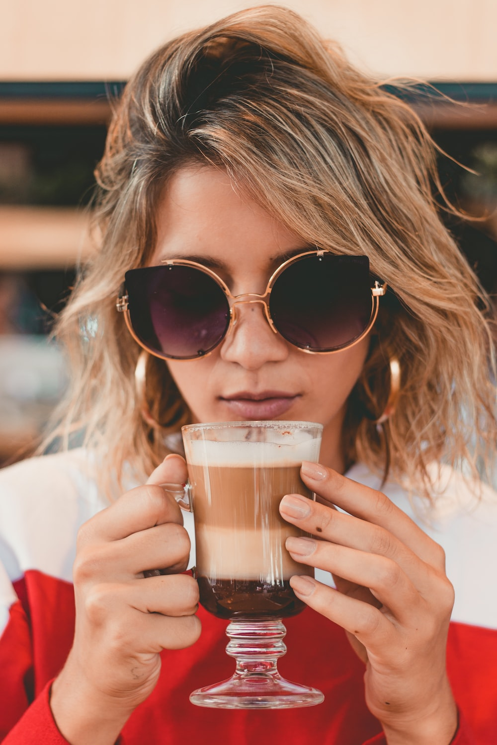 woman holding clear footed mug about to drink a coffee