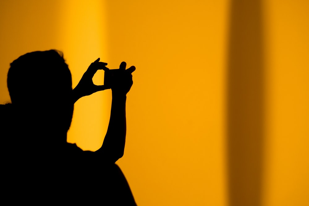 silhouette of man taking photo using camera