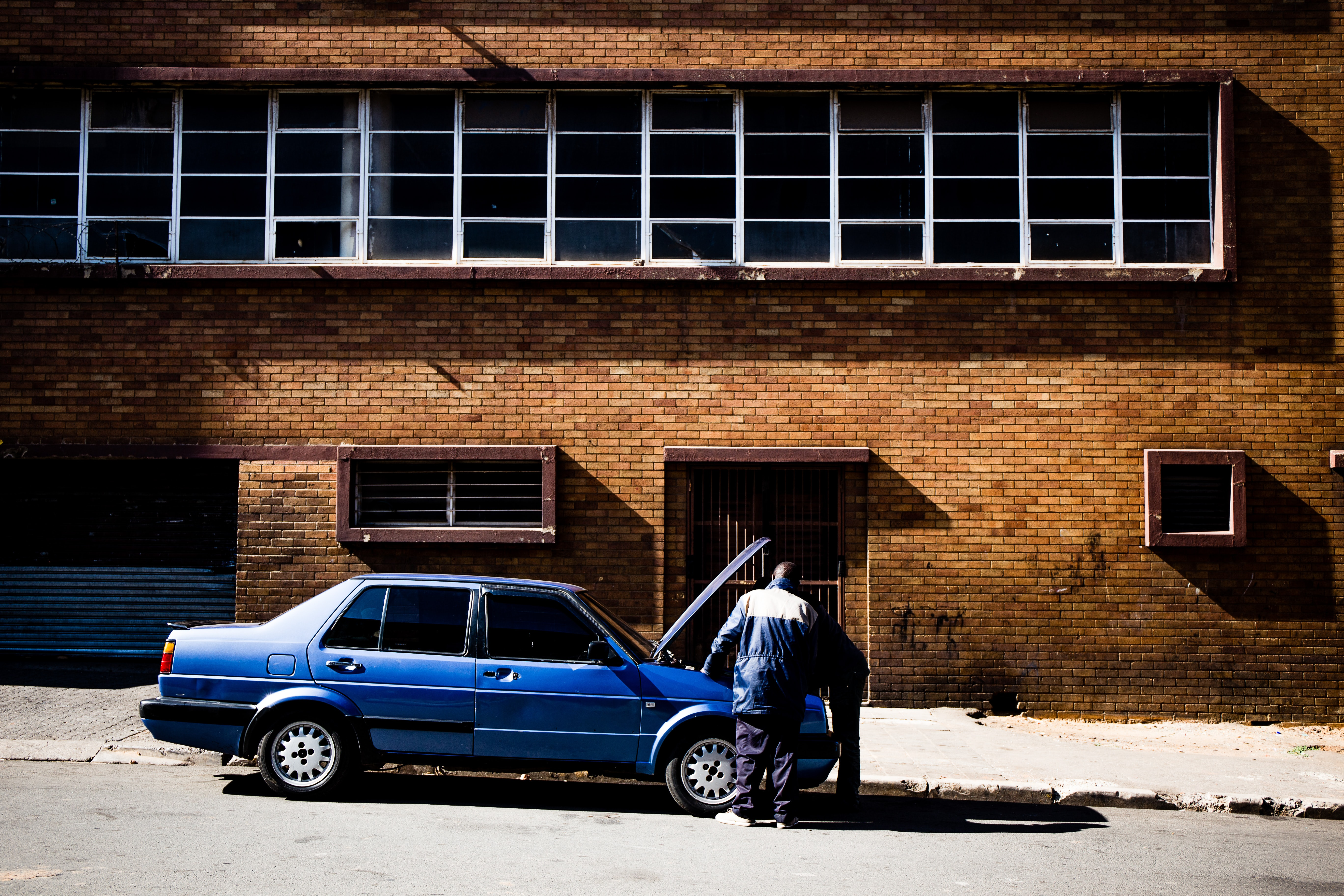 two men fixing up blue car