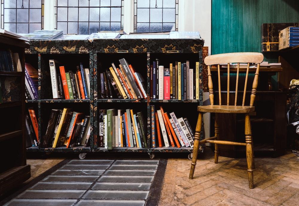 brown wooden windsor chair near black wooden bookshelf