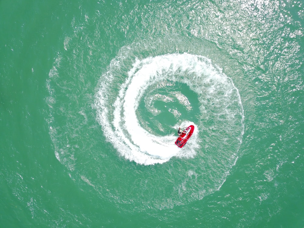 aerial photography of red personal watercraft circling on water at daytime